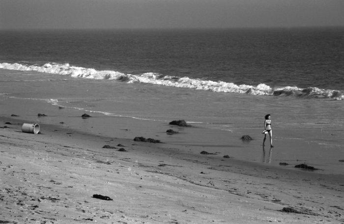 Young woman in bikini walking on Malibu beach