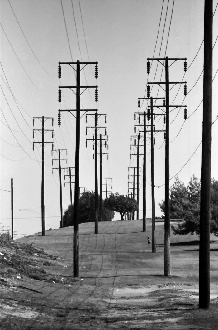 Child playing at the foot of electric pylons