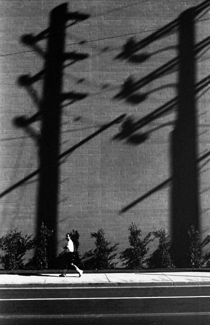jogger in the shade of giant pylons