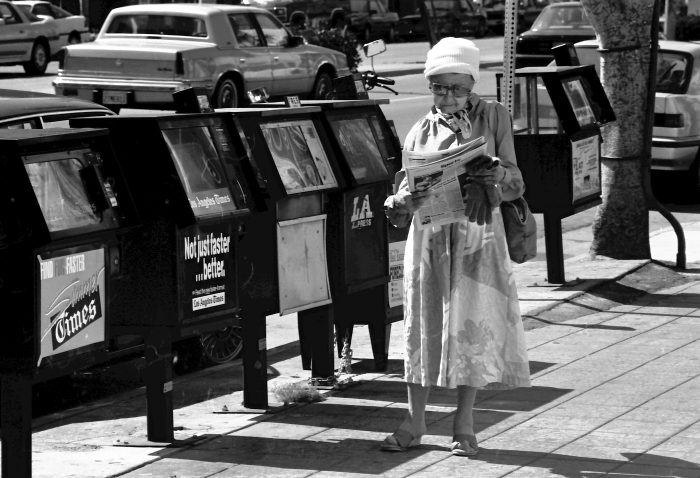 Old lady reading newspaper in the street
