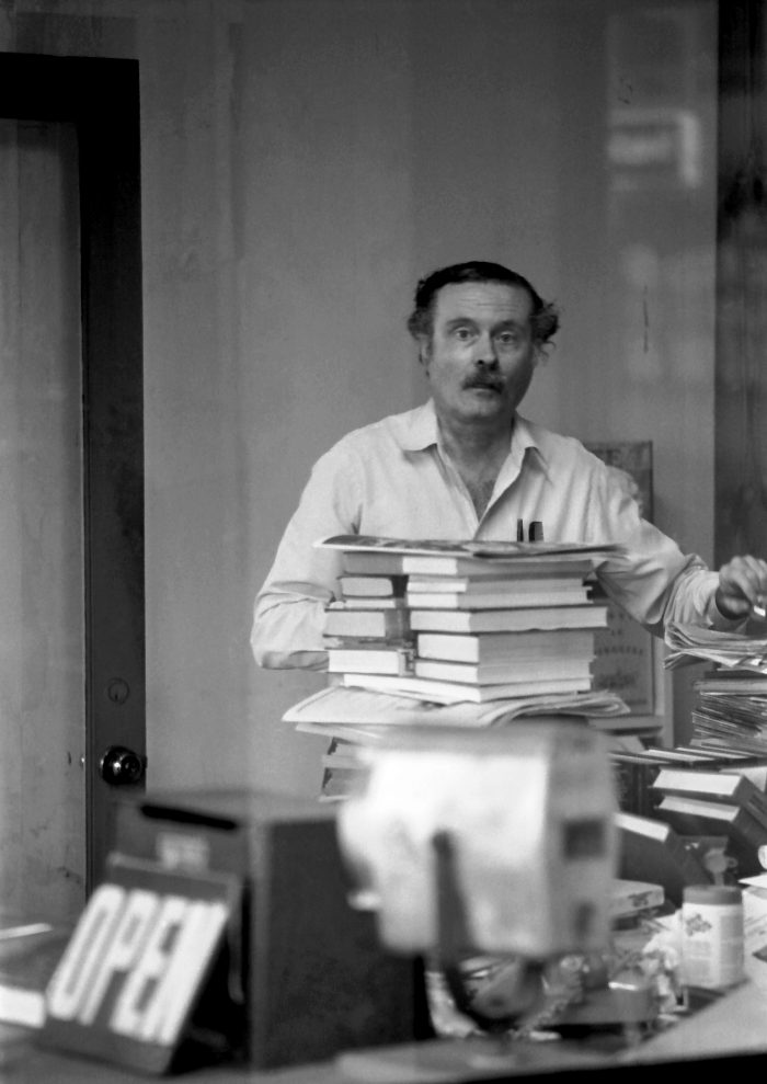 Bookseller in his store behind his books